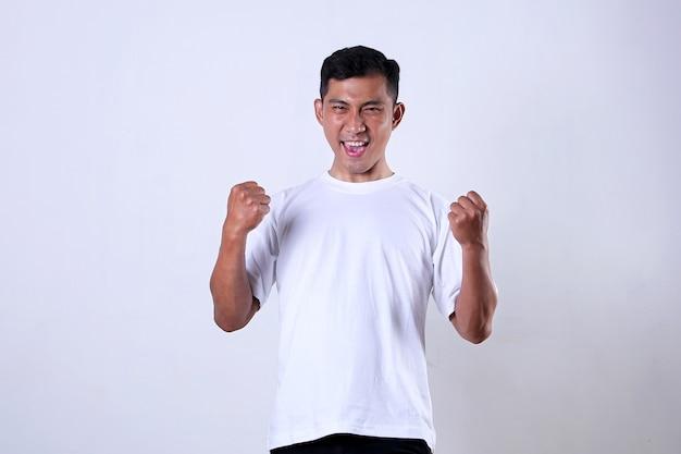 Азиатский мужчина в белом с выражением, полным триумфа и энтузиазма, изолированного на белом фоне