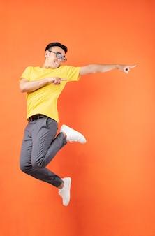 주황색 벽에 노란색 티셔츠 점프에서 아시아 남자