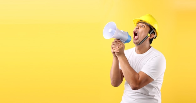Asian man industry worker or engineer shouting through a megaphone, happy excited raising his fists on yellow background in studio with copy space,concept  international labor day.