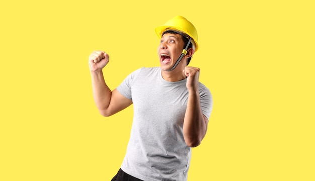 Asian man industry worker or engineer working an architect builder happy excited raising his fists on yellow background in studio with copy space.
