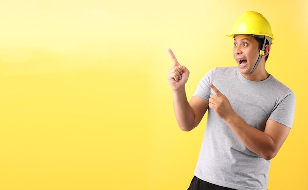 Asian man industry worker or engineer working an architect builder pointing finger on yellow background.