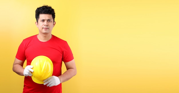 Asian man industry worker or engineer working an architect  on yellow wall ,concept international labour day.