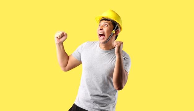 아시아 남자 산업 노동자 또는 건축가 작성기 작업 엔지니어 행복 복사 공간 스튜디오에서 노란색 배경에 그의 주먹을 제기 흥분.
