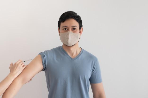 アジア人男性はcovidのウイルス対策の概念のためのワクチンを注射されています
