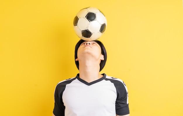 アジア人男性が頭でボールをバウンドしている