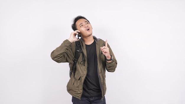 アジア人男性が白いスペースに電話をかけたり、物事をした