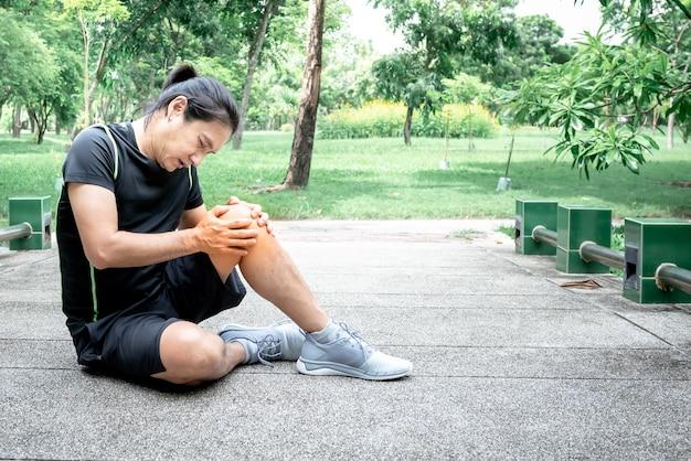 Азиатский мужчина в настоящее время получил травму колена во время тренировки в парке из-за остеоартрита