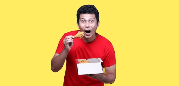 アジア人男性は黄色の背景にフライドチキンを美味しく食べています