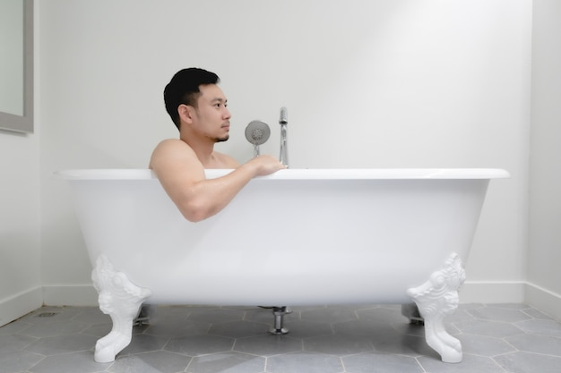 Asian man is having a good time in bathtub.
