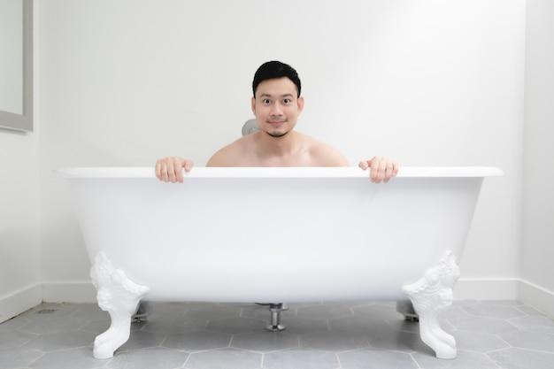 Asian man is having a good time in a white bathtub.