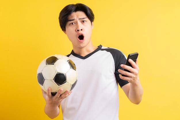 アジア人男性がボールを持って携帯電話を手に持っています