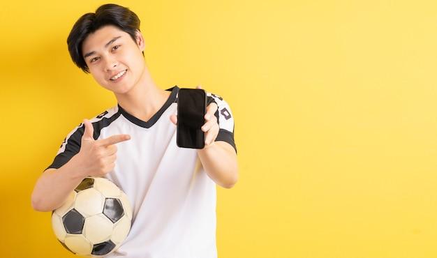 アジア人男性がボールを持って、空白の画面で電話を指しています