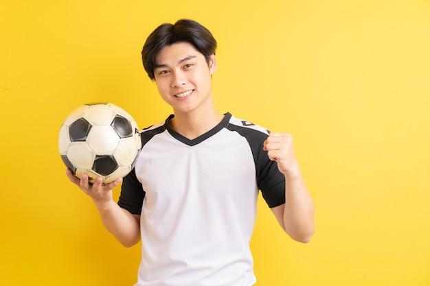 アジア人男性がボールを持って勝ち誇った表情を見せている