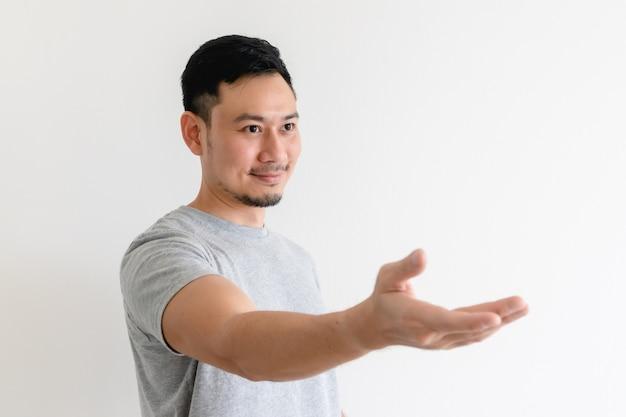 アジア人の男性は、招待状の手振りをしている、または助けを提供しています。