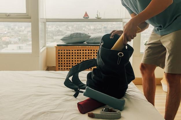 アジア人男性は旅行の準備ができて彼のバックパックを詰めています。