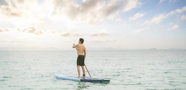 Азиатский мужчина гребет на доске sup, гребной стоя в океане во время заката, летние каникулы, каникулы.
