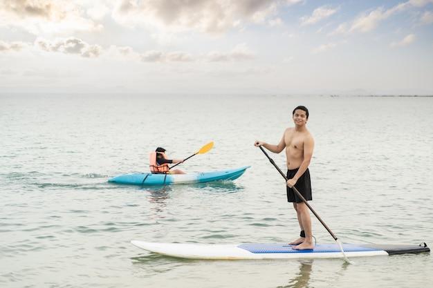 アジア人男性がsupボードを漕いでいます