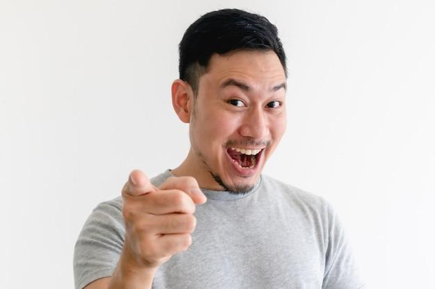 아시아 남자는 흥분된 표정으로 카메라를 가리키고 있습니다.