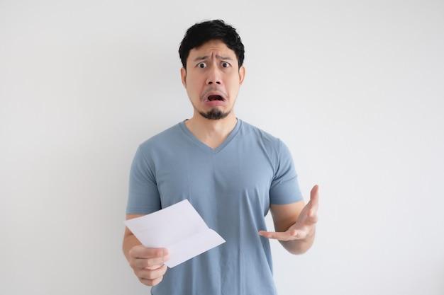 Азиатский мужчина грустен и шокирован письмом в руке на изолированном фоне.