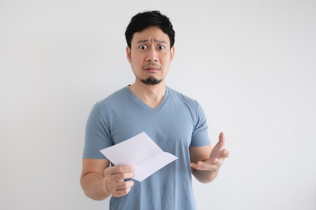 Asian man is sad and shocked by the letter in his hand on grey