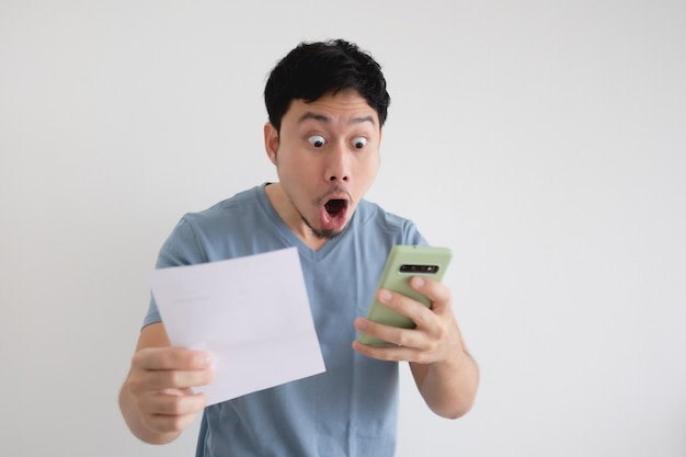 Азиатский мужчина шокирован счетом и смартфоном на изолированном фоне.