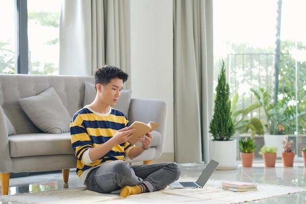 Азиатский мужчина сидит на полу с книгой и ноутбуком