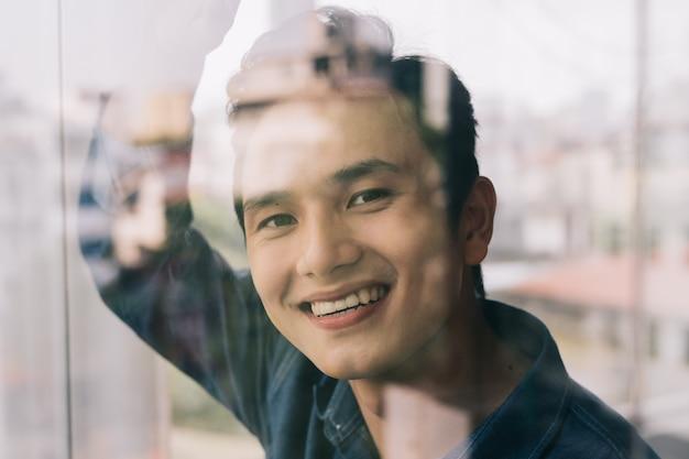 아시아 남자는 유리 문으로 웃