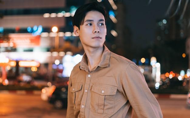 아시아 남자는 잃어버린 느낌 밤에 거리에서 걷고있다