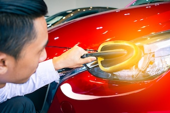 Asian man is wipping car with LED headlight