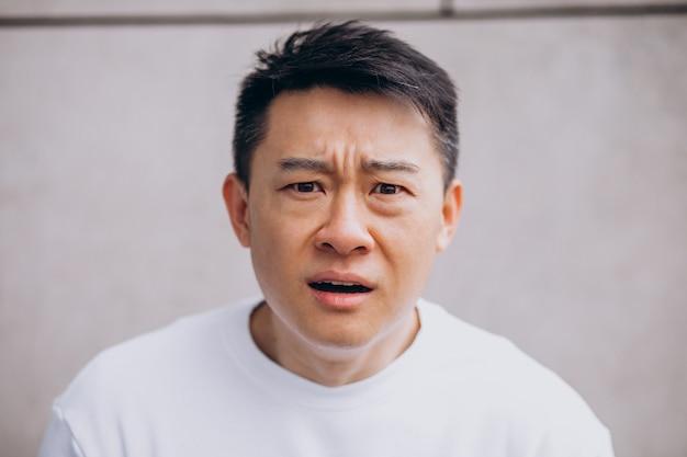 Uomo asiatico isolato che esprime emozioni