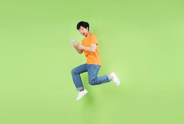 Азиатский мужчина прыгает и держит смартфон, изолированный на зеленом