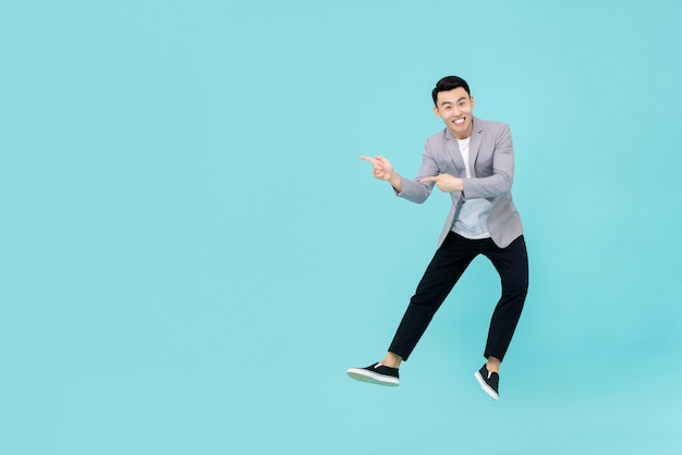 Asian man jumping and pointing fingers