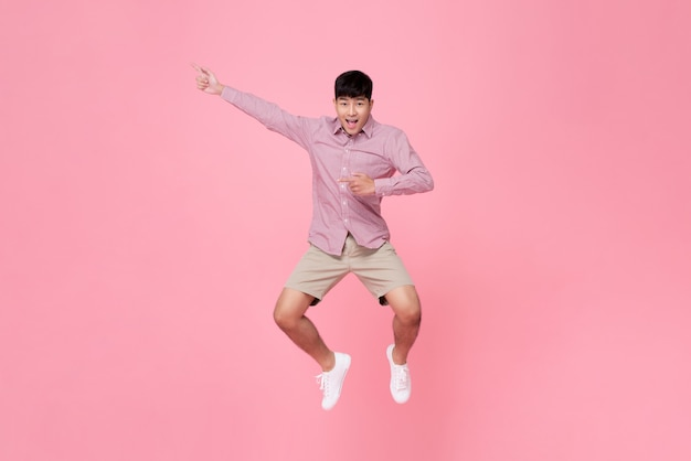 Asian man jumping with hand pointing aside