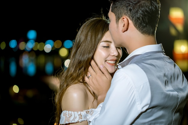 Asian man kissing his girlfriend head. at sweet night.