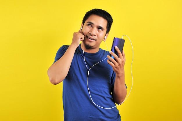 Азиатский мужчина слушает музыку со смартфона, глядя на копировальное пространство, изолированное на желтом фоне