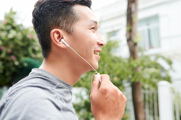 Азиатский человек слушая musi