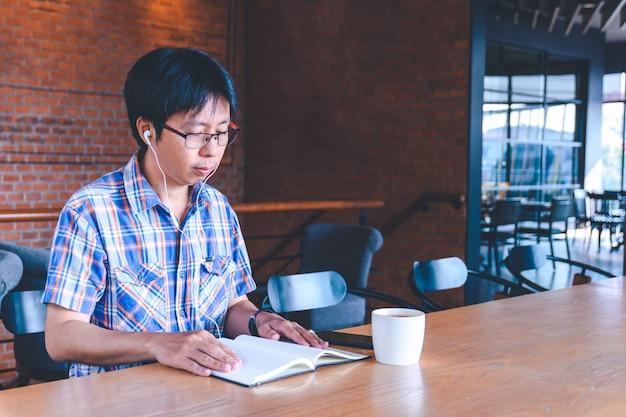 アジア人の男性がコーヒーショップで音楽を聴く