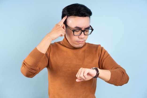 Asian man looking his watch on blue background