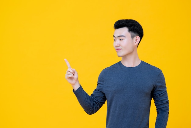 Asian man looking sideways and pointing finger aside to empty space