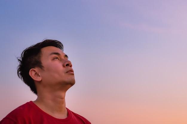空を見上げるアジア人男性。感情的な表情。