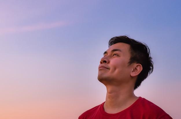 空を見上げるアジア人男性。ポジティブなメンタルヘルスと感情の表情。
