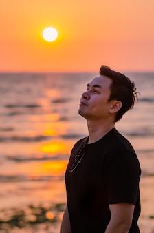 ビーチの背景に夕日と空を見上げるアジア人男性。ポジティブなメンタルヘルスと感情の表情。