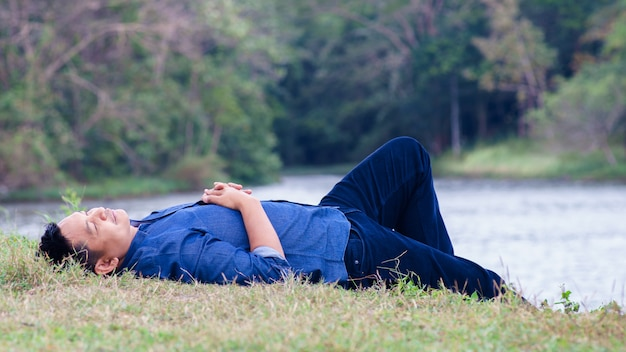 Asian man lying on the ground in the midst of nature with happy and comfort.