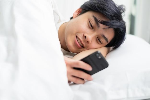 ベッドに横になって電話を使用しているアジア人男性