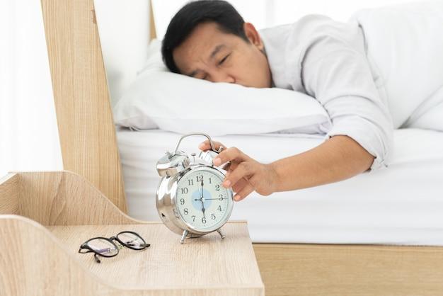 오전 6시에 아침에 알람 시계를 끄는 침대에 누워있는 아시아 사람