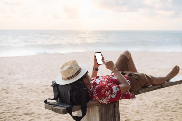 Asian man lying with smartphone on a beach