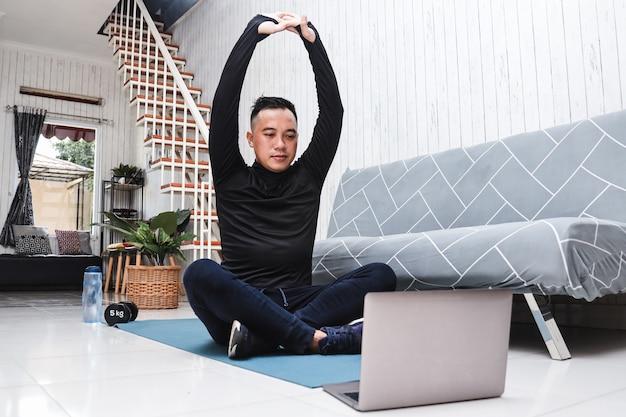 アジア人男性が指導のためにラップトップを使用して自宅で屋内でストレッチ運動をする