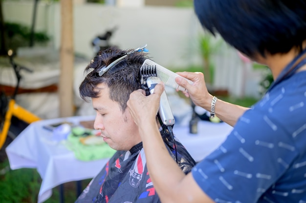 自宅で散髪やサロンビジネスをしているアジア人男性。庭の屋外理髪店。社会的距離と新しい通常のライフスタイル。