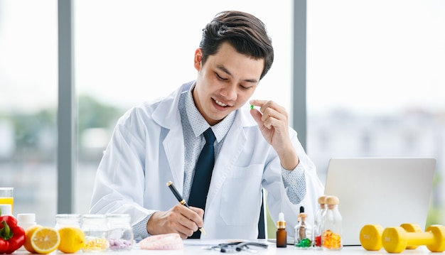 Asian man in medical uniform showing pill and making notes while working in modern clinic