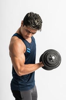 Мышцы азиатского мужчины поднимают тяжести гантелей с энергией на бицепс